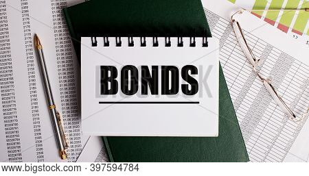 On The Desktop Are Reports, Glasses, A Pen, A Green Diary And A White Notebook With The Words Bonds.