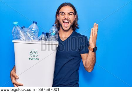Young handsome man holding recycling wastebasket with plastic bottles celebrating victory with happy smile and winner expression with raised hands