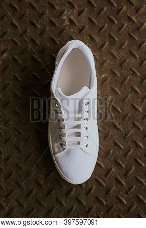 Single white canvas sneakers on metal floor