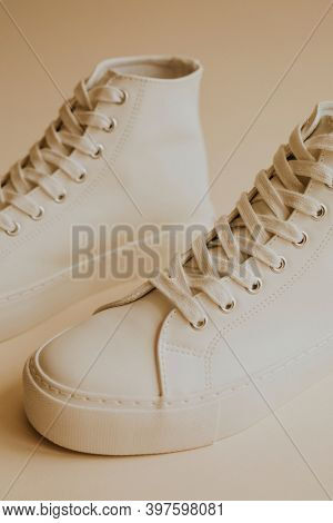 White high top sneakers on beige