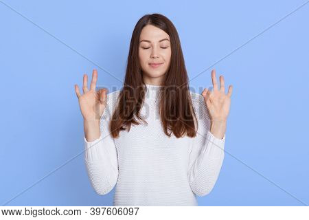 Photo Of Relaxed European Woman Shows Zen Or Okay Sign, Meditates Indoor Against Blue Wall, Has Calm