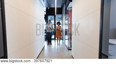 Mixed race business people wearing face masks in creative office. man and woman walking in hall and discussing work. social distancing protection hygiene in workplace during covid 19 pandemic.
