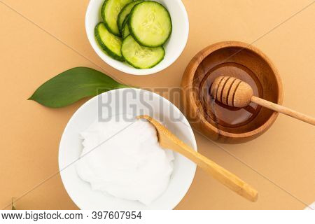 Bowls with yoghurt, cucumber and dressing on yellow background. fresh whole foods healthy living copy space concept.