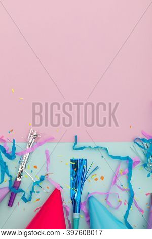 Party hat, party blowers and confetti on pink and blue background. happy birthday party celebration fun concept.