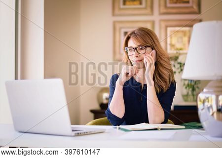Shot Of Middle Aged Businesswoman Using Mobile Phone And Laptop While Sitting At Desk And Working Fr