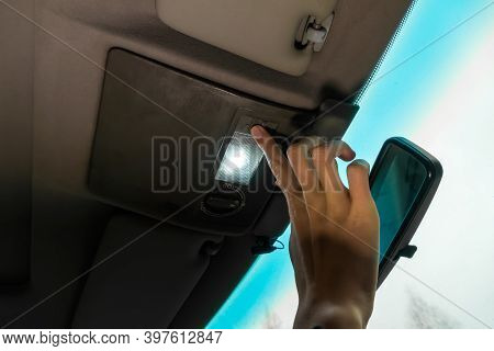 Womans Hand Turns On The Interior Lighting In The Car Close-up