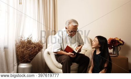 Asian Grandfather Reading Book Sit On Sofa To Granddaughter Listening And Sit On Floor At Home. Chee