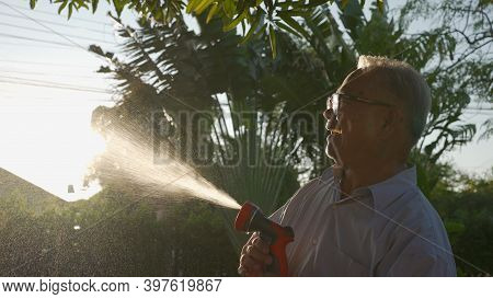 Happy Asian Senior Grandpa Pouring Water From A Hose. Funny Grandparent And Grandkid Playing With Ho
