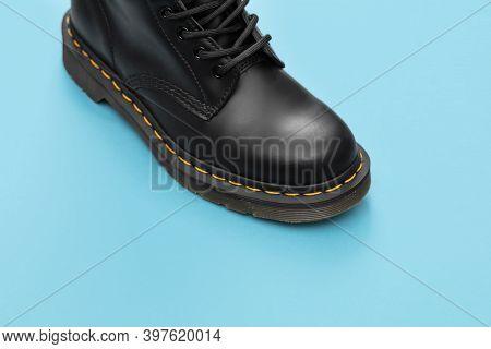 Black Boot On The Blue Background . Fashion Shoes Still Life. Classic Unisex Black Lace-up Fashion C