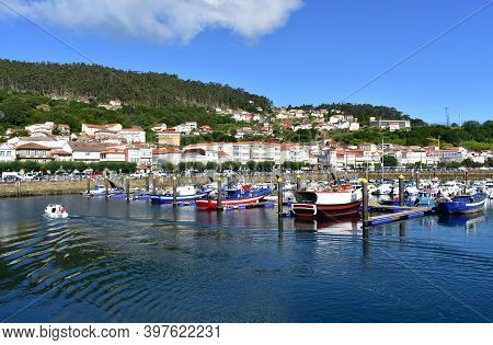 Muros, Spain. June 18, 2020. Harbor And Coastal Village With Galician Fishing Vessels And Sailing Bo