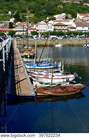 Muros, Spain. June 18, 2020. Harbor And Coastal Village With Traditional Galician Fishing Vessels An