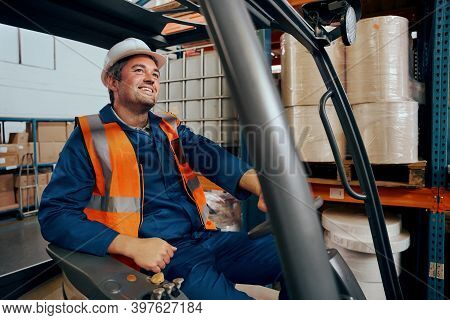 Happy Engineer Operating Forklift Truck In Warehouse