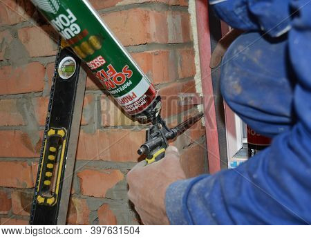 Kyiv, Ukraine - November  02, 2020: A Professional Window Installer Is Sealing The Pvc Window, Filli