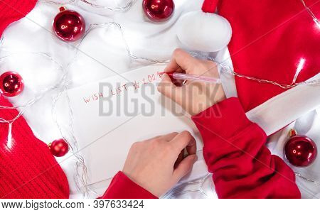 Write A Wish List For Santa With A Red Pen On A Blank White Sheet. Red Christmas Balls, Santa Hat An
