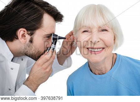 Hearing Exam. Senior Woman During A Hearing Test, An Audiologist With An Otoscope Checking Ear Of El