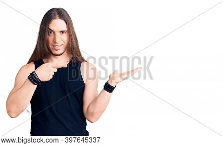Young adult man with long hair wearing goth style with black clothes amazed and smiling to the camera while presenting with hand and pointing with finger.