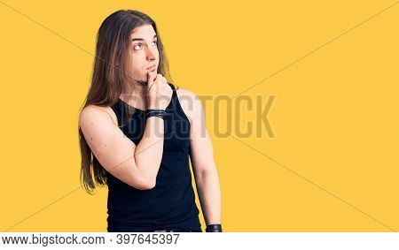 Young adult man with long hair wearing goth style with black clothes thinking worried about a question, concerned and nervous with hand on chin