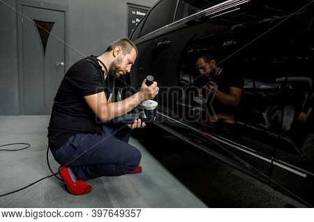 Horizontal Shot Of Man Auto Service Worker, Wearing Black Clothes, Putting Special Polish Wax Or Cre
