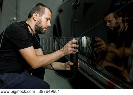 Car Detailing And Polishing Concept. Professional Caucasian Male Car Service Worker, Wearing Black U