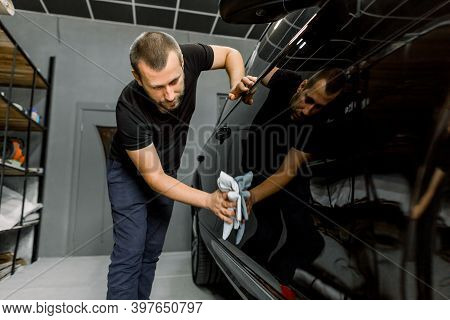 Handsome Young Caucasian Man, Professional Worker Of Car Detailing Service, Polishing Black Car With