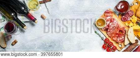 Antipasto Background. Red And White Wine With Meat And Cheese Appetizers. On A Rustic Background.