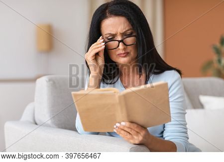Portrait Of Mature Woman Touching Glasses Trying To Read Book, Having Difficulties Seeing Text Becau