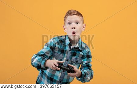 Excited Boy Playing Video Game With Joystick Alone On Yellow Studio Background, Panorama With Copy S