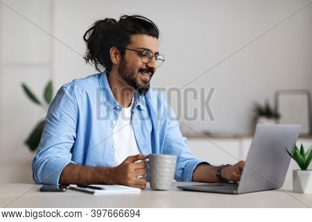 Pros Of Freelancing. Positive Indian Freelancer Guy Drinking Coffee And Working On Laptop At Home Of