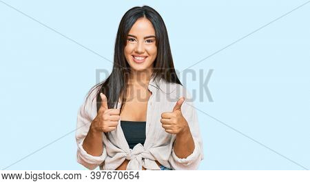 Young beautiful hispanic girl wearing casual clothes success sign doing positive gesture with hand, thumbs up smiling and happy. cheerful expression and winner gesture.