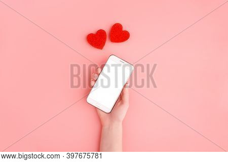 Close Up Of Mobile Smart Phone With Red Hearts On Pink Pastel Background, Copy Space. Flat Lay, Top