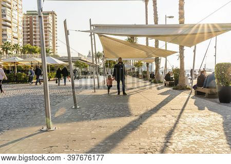 Malaga / Spain - May 18th, 2020: Father And Daughter Walking On Paseo Del Muelle Uno On Sunny Day