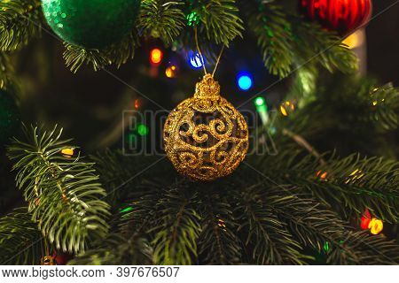 Beautiful Christmas Tree With Gold Toy On Branches Close Up. Concept Of A New Year Atmosphere And Fe