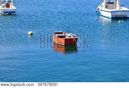 Red Wooden Rowboat Floating On The Sea Moored In A Harbor. Rias Baixas, Galicia, Spain.