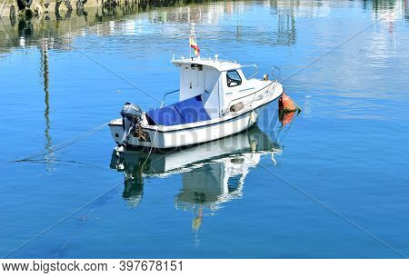 Portosin, Spain. June 19, 2020. Small Galician Fishing Boat With Water Reflection Moored In A Harbor