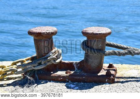 Rusty Iron Mooring Post Close-up In A Harbor At Famous Rias Baixas In Galicia Region. Spain.