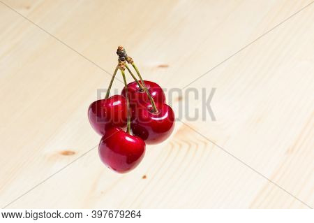 Four Organic Sweet Cherries Isolated On A Wooden Background