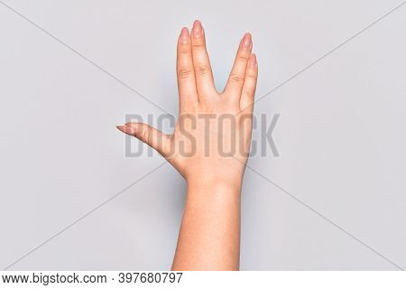 Hand of caucasian young woman greeting doing Vulcan salute, showing back of the hand and fingers, freak culture