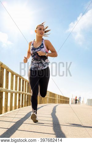 Full Length Front View Portrait Of Young Woman Jogging On Bridge. Girl In Sportswear Running On Sunn