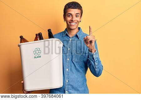 Young african amercian man holding recycling wastebasket with glass smiling with an idea or question pointing finger with happy face, number one