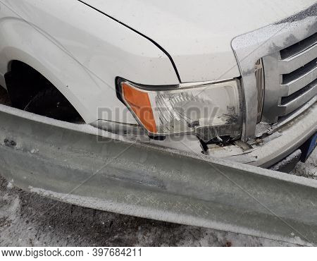 Car Crash Fender Bender With White Truck And Broken Bumper Against Road Barrier