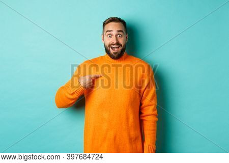 Excited Man Pointing At Himself, Looking Amazed And Happy, Being Chosen, Standing Over Light Blue Ba