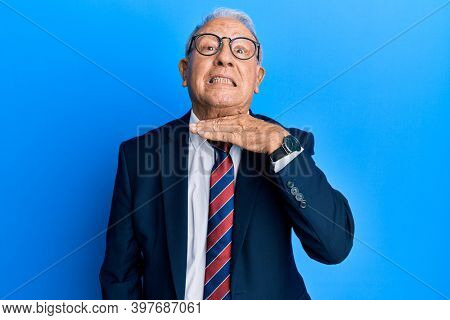 Senior caucasian man wearing business suit and tie cutting throat with hand as knife, threaten aggression with furious violence