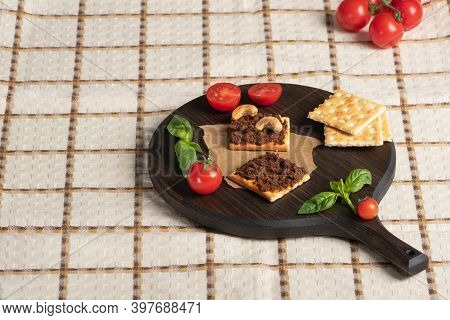 Square Crispbread Crackers With Vegetable Pate On  Round Dark Cutting Board. Cherry, Cashew And Gree