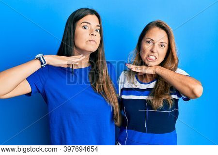 Hispanic family of mother and daughter wearing casual clothes over blue background cutting throat with hand as knife, threaten aggression with furious violence