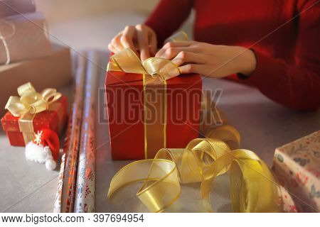 Packing And Tying A Yellow Bow On A Red Gift Box Before The Christmas Holidays.
