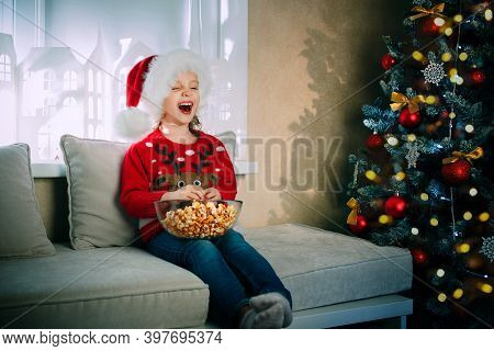 A Laughing Girl In Santa Claus Hat On Christmas Eve Enjoys Popcorn While Watching Tv
