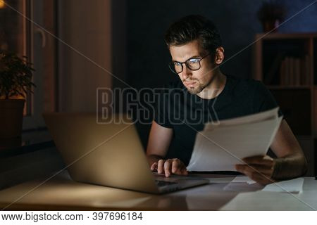 Portrait Of Tired Focused Young Man In Glasses Working Remotely Late At Night At Home Office With Co