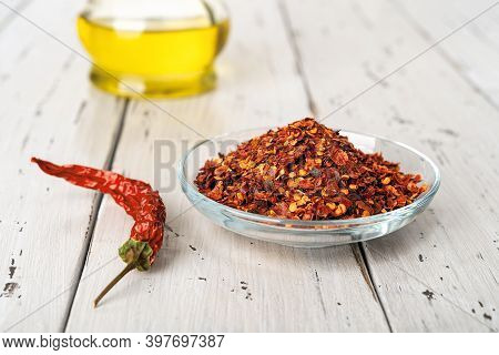 Red Hot Pepper Flakes In A Glass Saucer And Dry Wrinkled Pepper Pod On A Rustic Wood Table. Natural