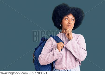 Young african american girl holding student backpack serious face thinking about question with hand on chin, thoughtful about confusing idea