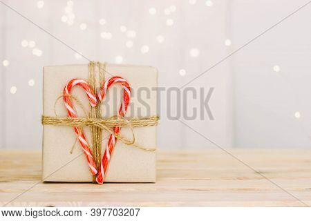A Gift Box With Christmas Lollipops. Gift Box On Wooden Background. Christmas Striped Candy Canes. T